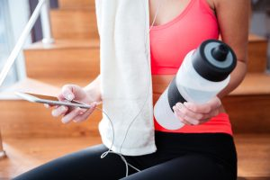 woman at gym with water and phone